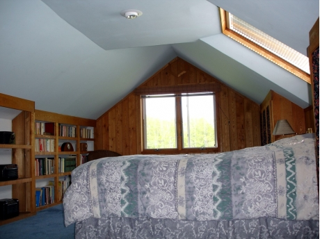 Master bedroom with skylight above bed and view over front fields.