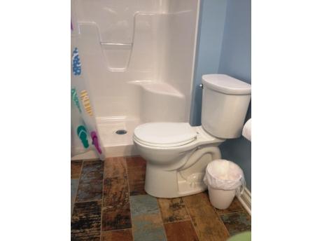 ceramic tile bathroom with window & fan; shower has built in seat