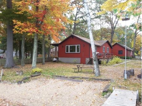 Fall colors set off the sandy beach and red cottage proximity to the lake.