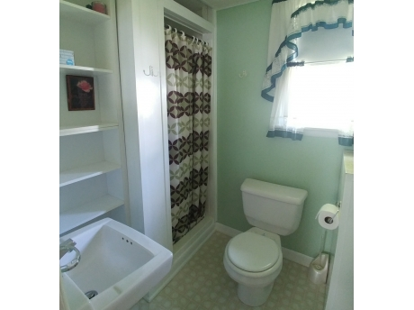 Very Clean Bathroom with Shower and plenty of shelving.