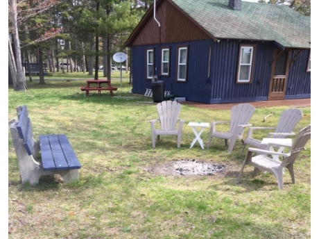 Bench and chairs ready for camp fire. Marsh-mellow sticks hanging inside.