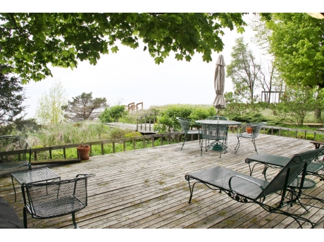 Private tiered deck and stairs lead to the beach