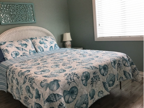 Main floor bedroom with ceiling fan queen bed